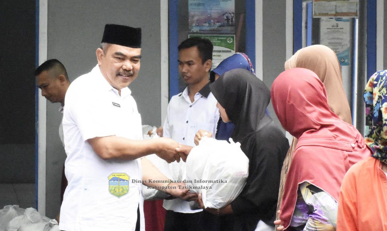 Plh Sekda Kabupaten Tasikmalaya, Drs. Iin Aminudin m. Si, saat memberikan bahan pokok bersubsidi pada acara Operasi Pasar Murah di Desa